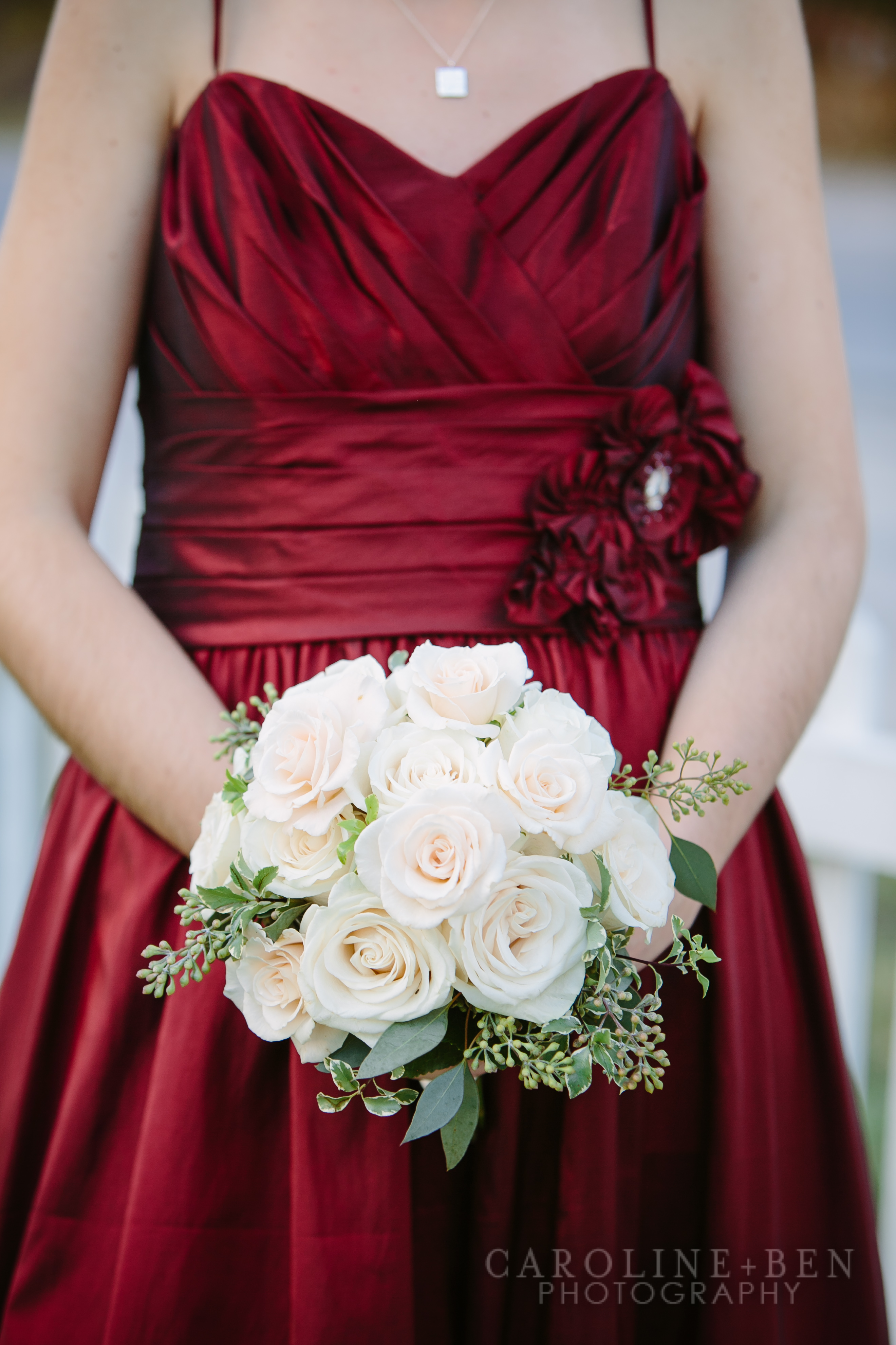 Lush open roses for the bridesmaids who were dressed elegantly in crimson.