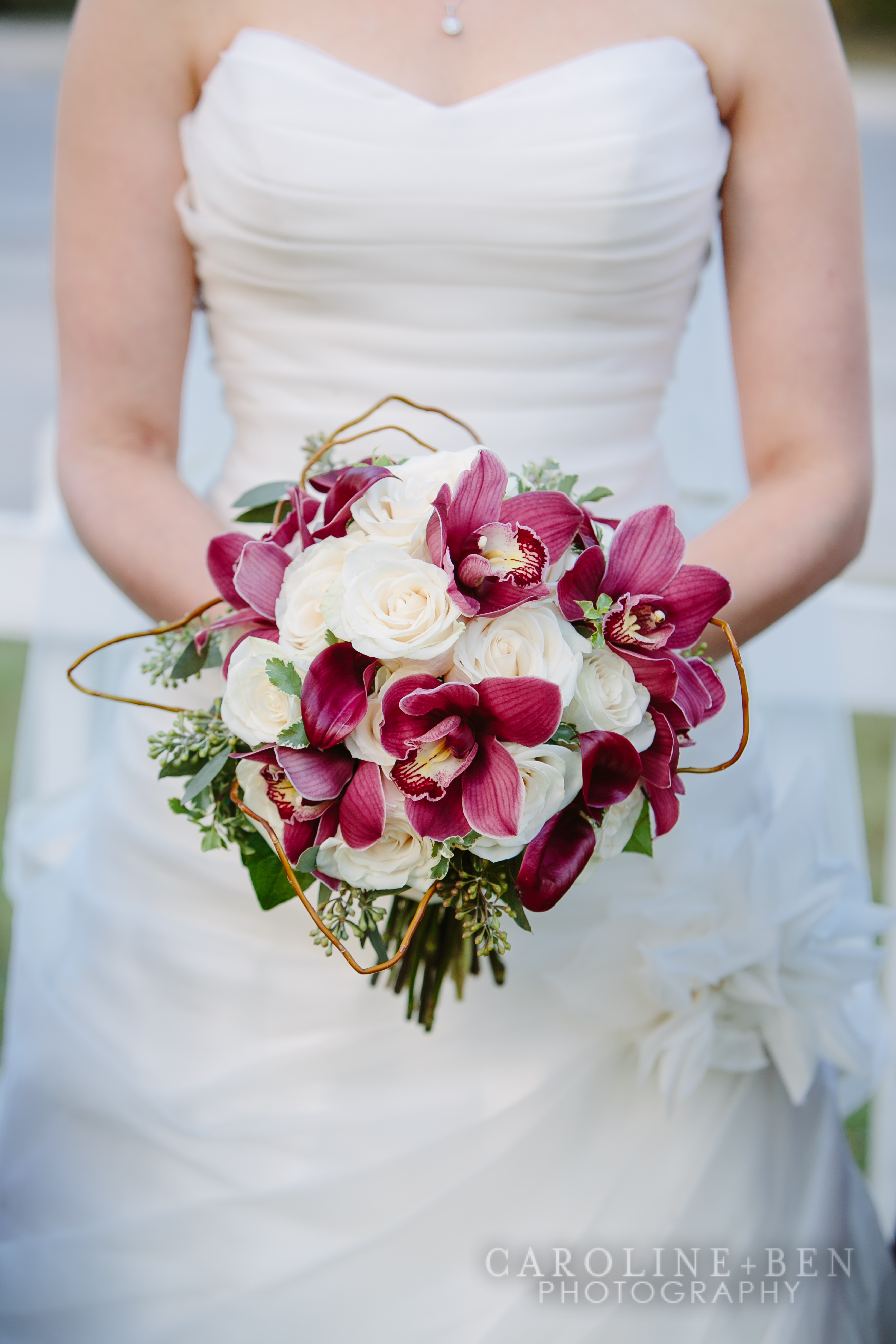 The brides bouquet with the contrasting crimson orchids and calla lilies.