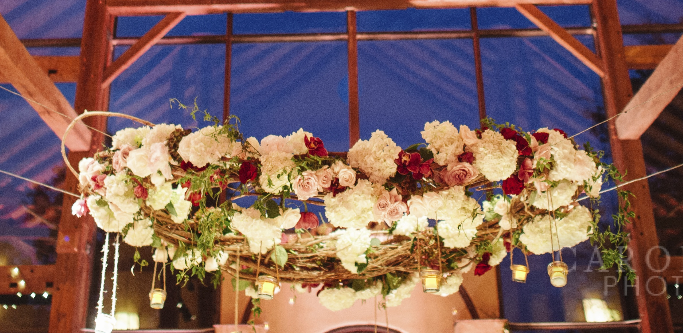 Lush wreath of florals suspended over dance floor.