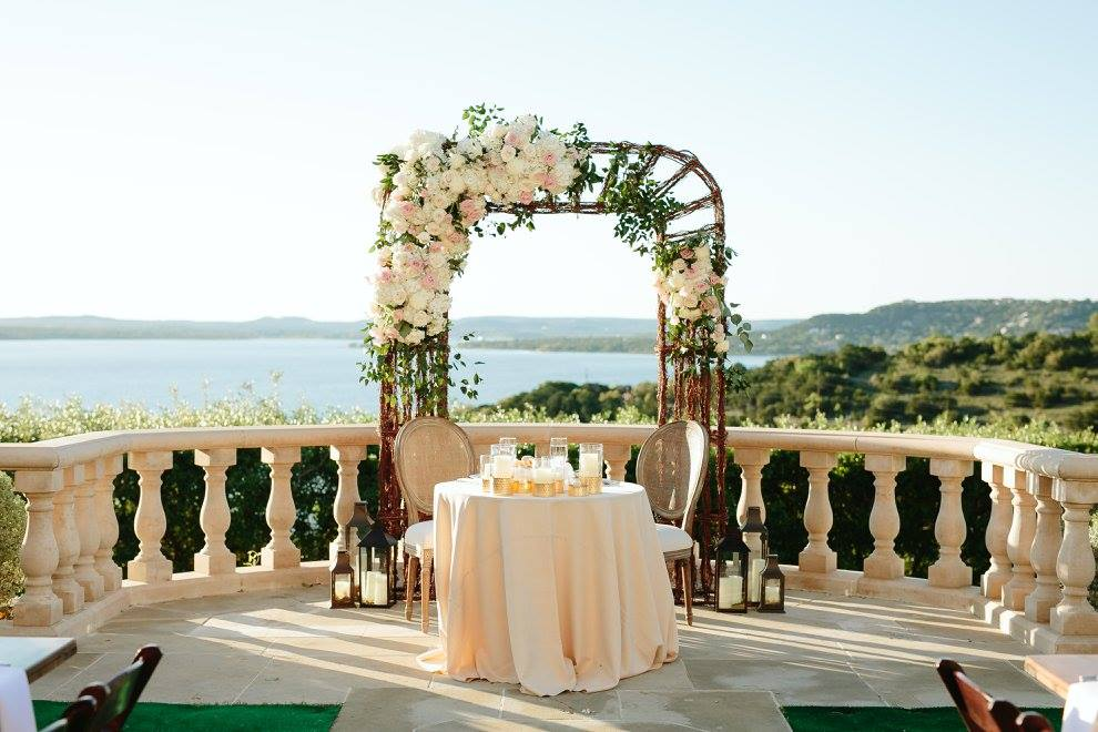 Willow arch with floral accents flanking sweetheart table.
