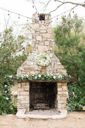 Outdoor ceremony with greenery garland decor and hydrangea wreath.