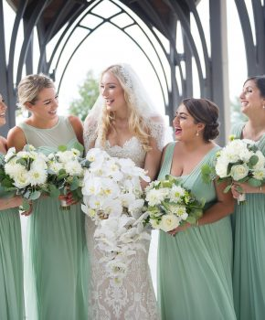 Smiling bride with cascading bouquet of phalaenopsis orchids