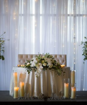 Sweetheart table with large florals/candles with low lush floral arrangement