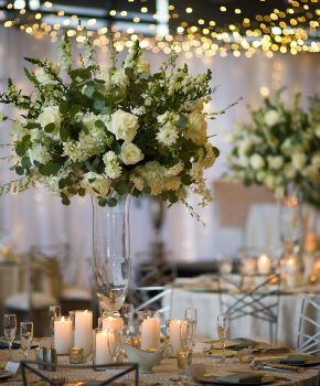 Tall clear vase wtih all white and green flower arrangements with pillar candle accents.