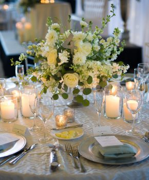 All white and green flower arrangement with candle accents.