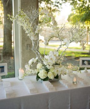 Silver manzanita branches with orchid accents for escort card display.
