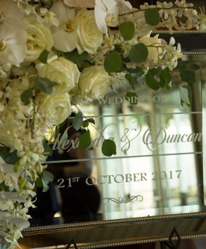 Mirrored welcome sign embellished with white and green flowers.