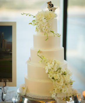 Wedding cake with fresh white flowers including orchids and roses.