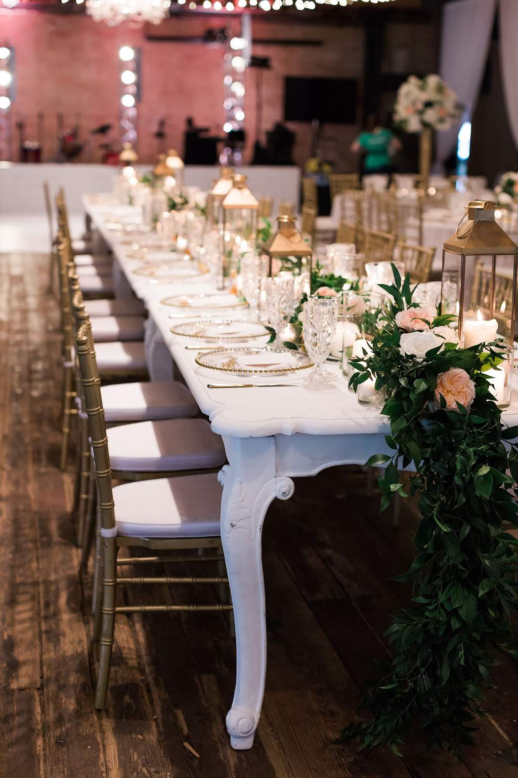 Head table with garland and lanterns.