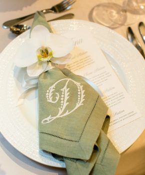 Custom monogrammed sage green dinner napkin on head table at wedding reception at Hotel Van Zandt with single orchid napkin placement.