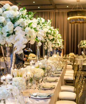 Head table at wedding reception with tall and low flower arrangements and candles, white, gold and sage green.