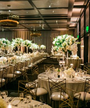 Luxurious all white centerpieces on garnier vase with floating candle accents at Hotel Van Zandt.