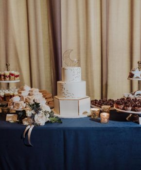Dessert table at wedding reception with celestial themed cake and cookies.